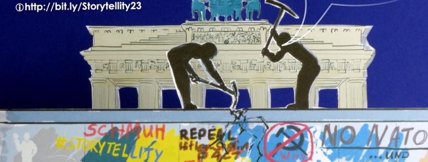 Zwei symbolische Männer hacken mit Spitzhacken auf die Berliner Mauer ein.